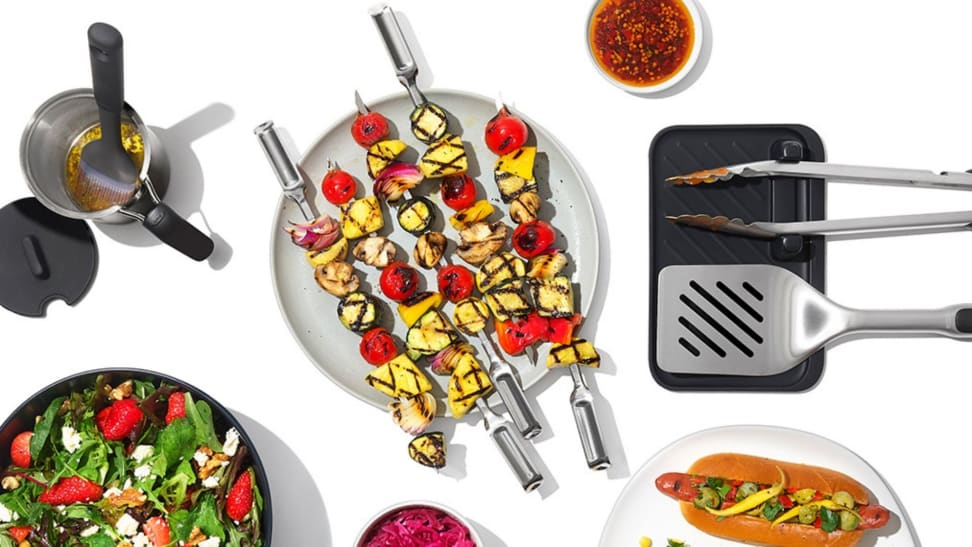 A top-down photo of grilled veggies, hotdogs, and the grilling tools used to good them.