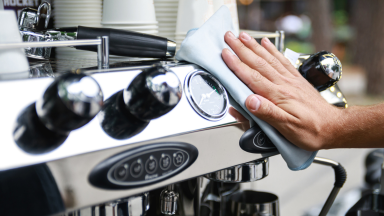 A barista wipes an espresso machine after a day of work.