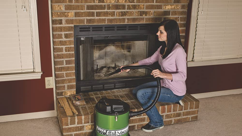 Woman using vacuum to clean fireplace.