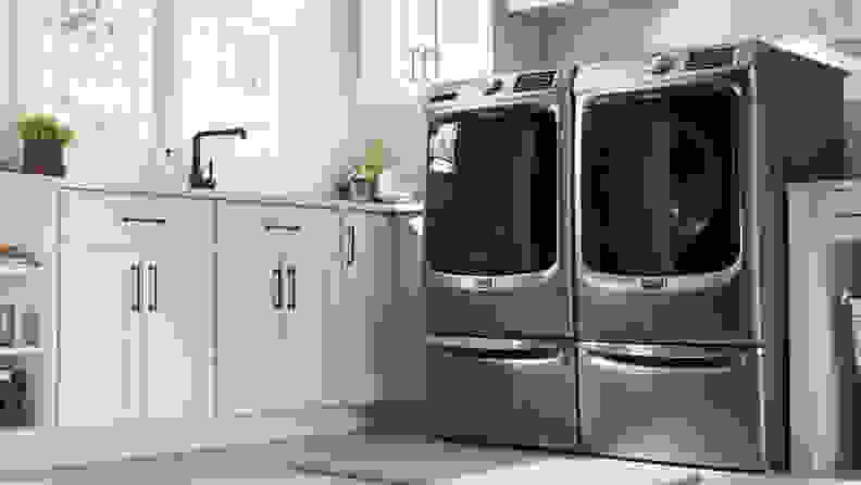 The Maytag MED6630HC beside a Maytag washer in a white kitchen.