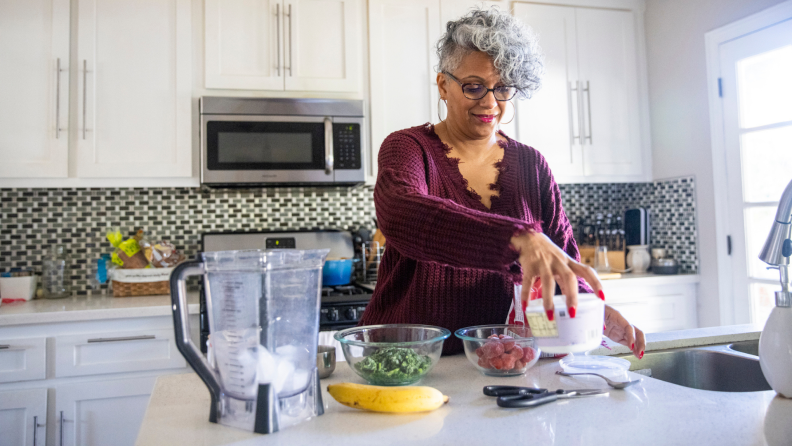 Older woman making a smoothie portion for one.