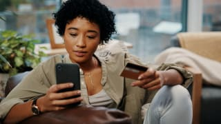 A woman sits in a chair holding her phone and credit card