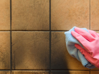 Hand with pink glove wiping down soot on a tile wall with a microfiber towel