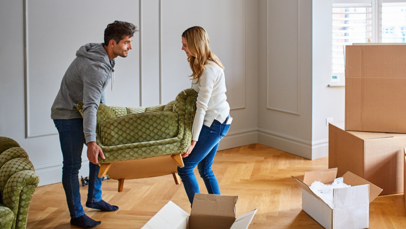 A couple moves furniture into their new home.