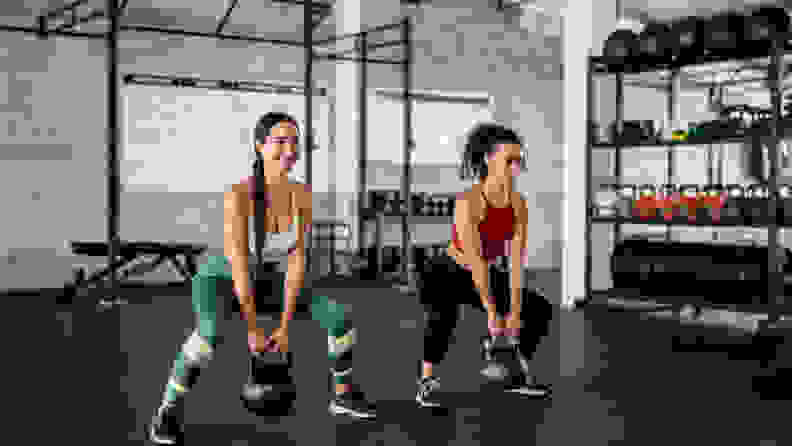 Two women squatting with kettlebells at the gym.