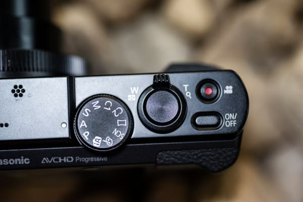 The top controls include a shutter release, zoom, record button, power switch, and mode dial.