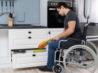 A man in a wheelchair puts away dishes in a kitchen.