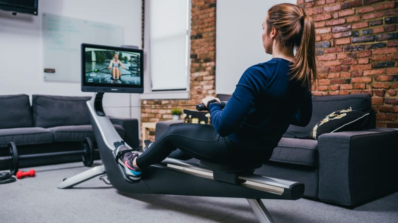 woman exercising on hydrow rowing machine.