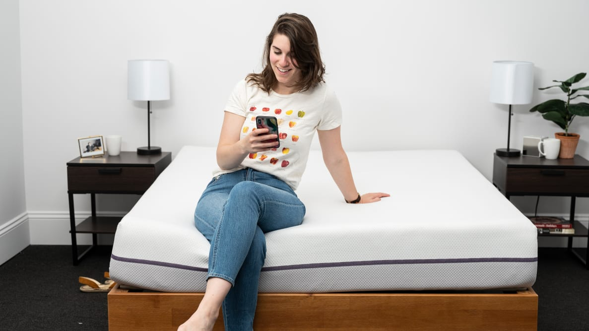 a woman sits on the foot of the Purple Mattress looking at her phone.