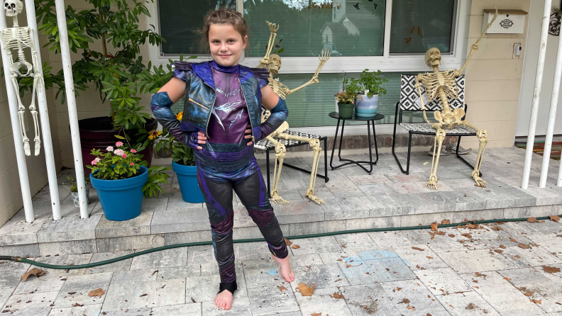 A girl dressed up as Mal from Descendants 3 standing on a porch decorated with skeletons
