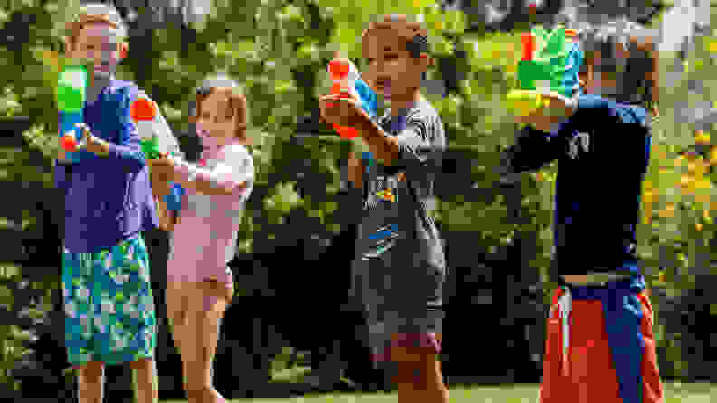 Four kids with all kids of super soakers