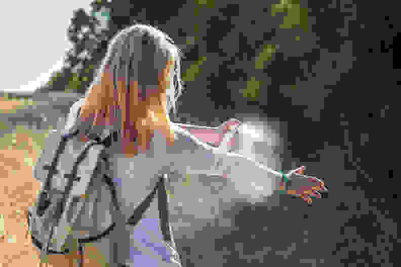 woman sprays bug spray outside forest