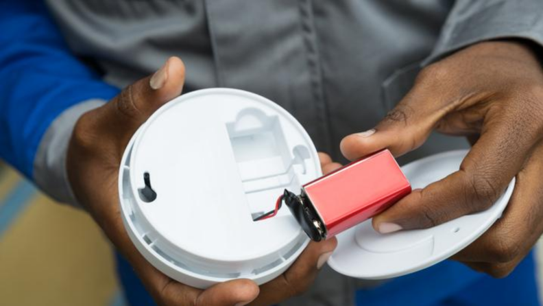 Man removing battery out of a smoke detector