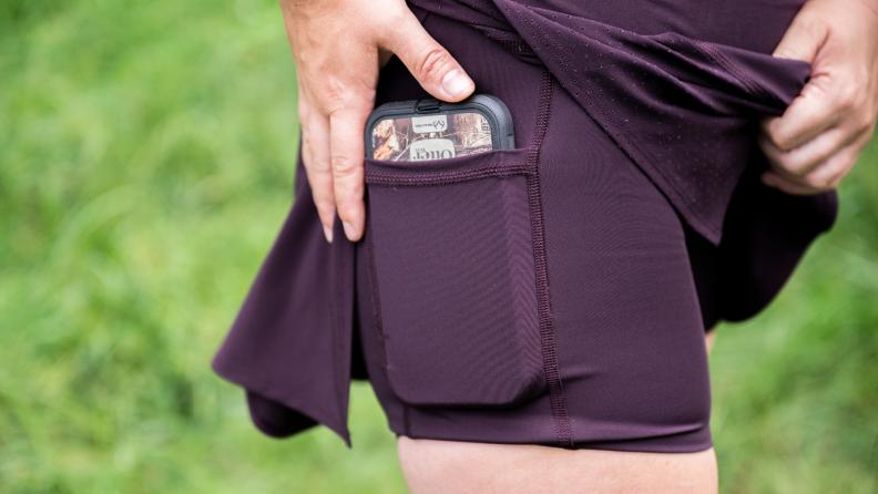 Girl puts her phone into a skort pocket.