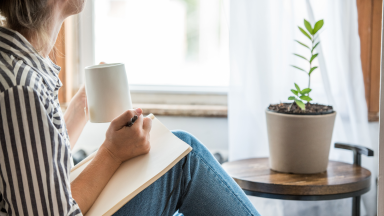 Woman staring at plant with a notebook in her hand