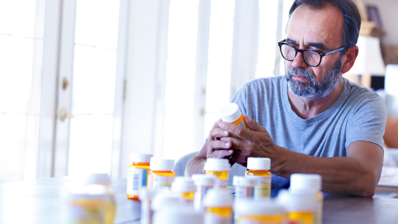 Person sitting at table surveying medication bottles.