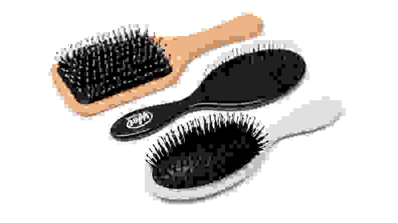 Three hair brushes lay side by side on a white surface.