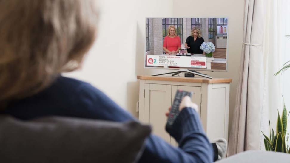 blonde person watching QVC channel on TV.