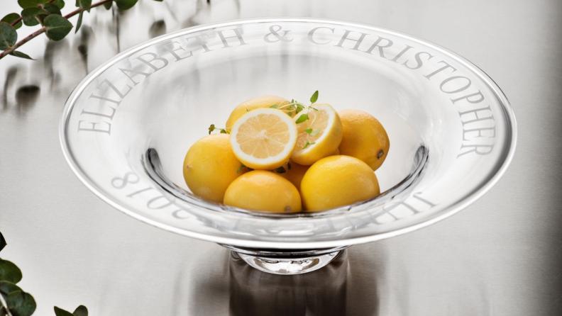 An engraved glass bowl holding some fresh lemons.