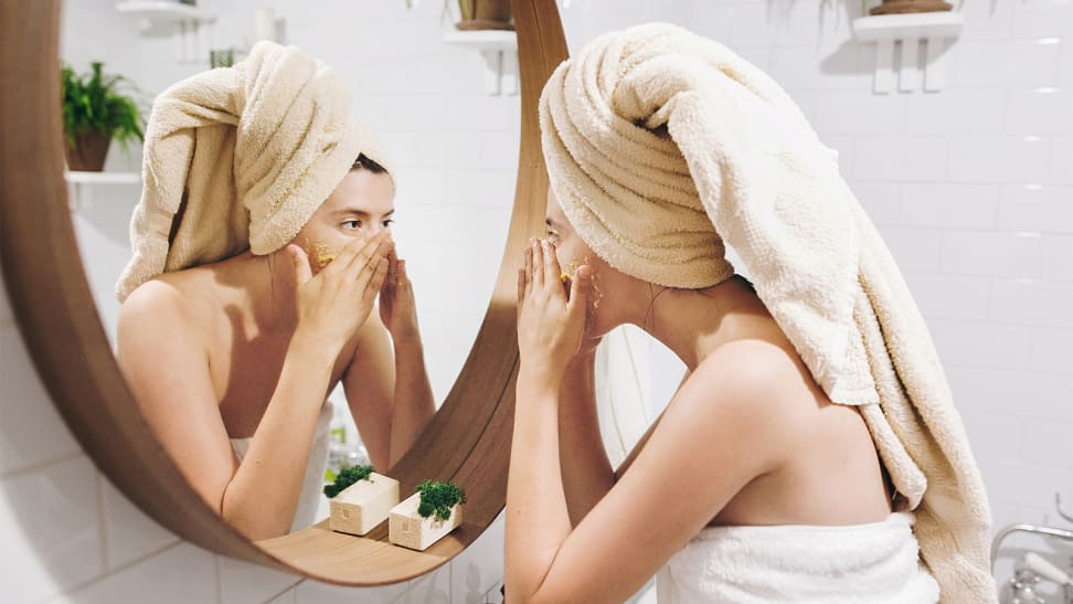 A photo of a woman applying moisturizer.