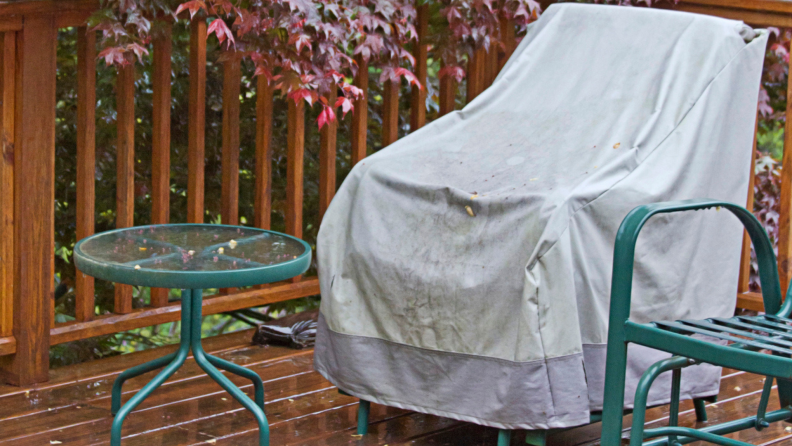 Patio chair covered in a protective patio covering next to a side table on a wet wood deck in the rain