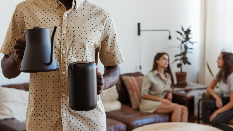 A person is holding a Fellow electric kettle on one hand and a Fellow French press on the other hand. Two people were chatting in the back.