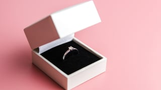 This is an engagement ring in a white box against a pink background.