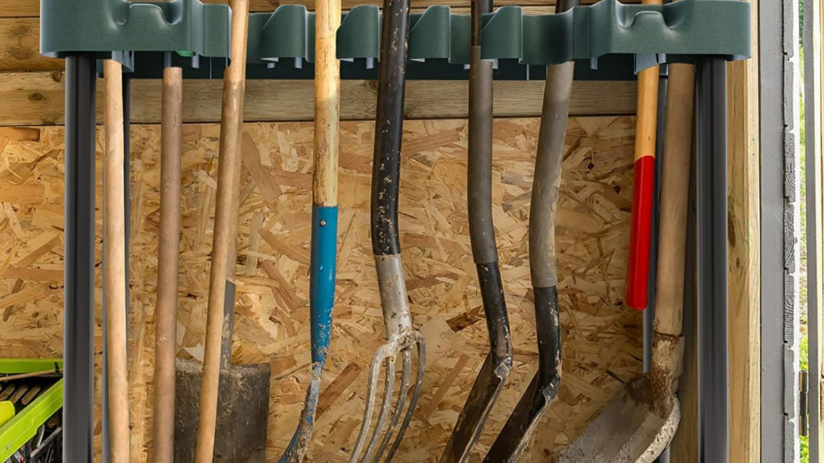 Garden tools hanging from an organizer.