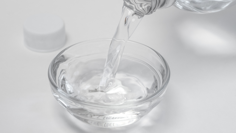 Pouring white distilled vinegar in a bowl.