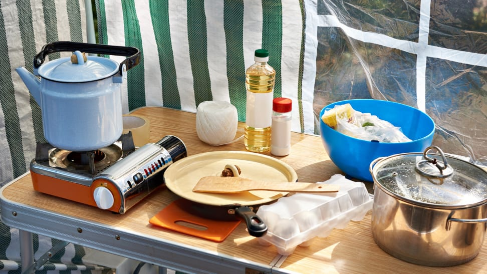 On an outdoor kitchen table, a portable stove is on the left corner with a kettle on top; to its right, a cutting board and some plates are stacked on top of each other. Condiment bottles are in the back. To the right, there's a large metal pot.