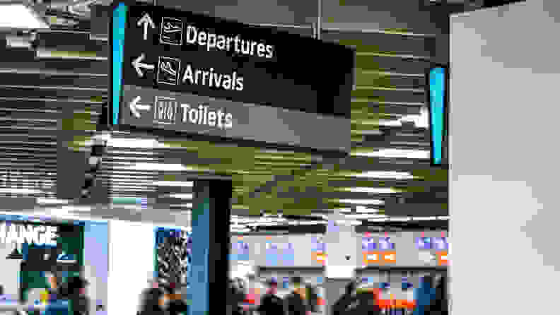 Blurred anonymous people walking under information table, under arrival, departure, and toilets sign at the airport.