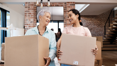 A parent and child move into a home with cardboard boxes.