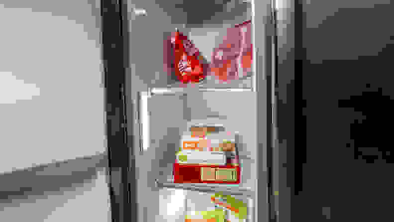 A close-up of the Frigidaire Gallery GRSC2352AF side-by-side refrigerator's freezer compartment, with some food