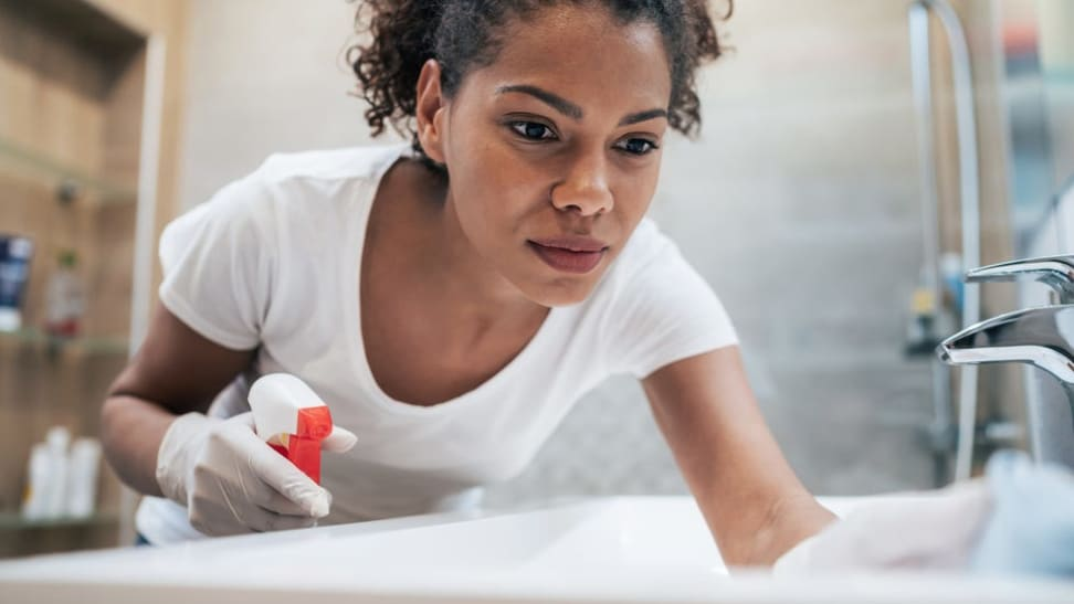 Person wearing white rubber gloves to clean sink surface in bathroom.
