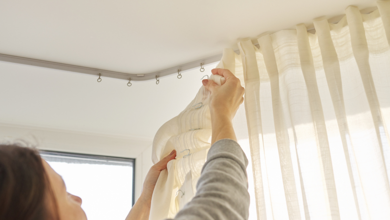 Woman hanging up new cotton curtains above her window
