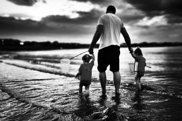 Danny Van Vuuren's photo of a man walking with two children on the beach was also a category winner. [Credit: Danny Van Vuuren/IPPA]