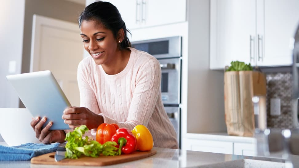 Woman looking at ipad with vegetables