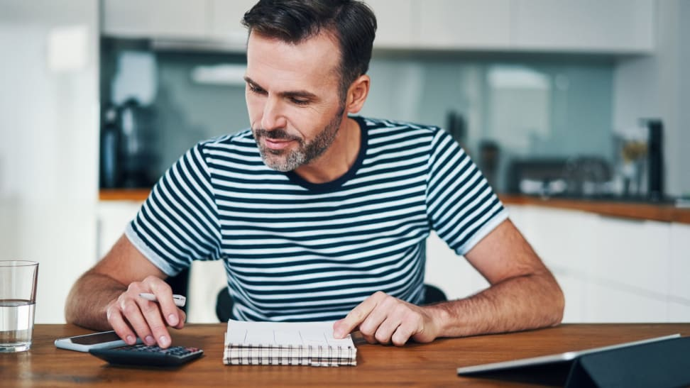 Man creating 50/30/20 budget with calculator