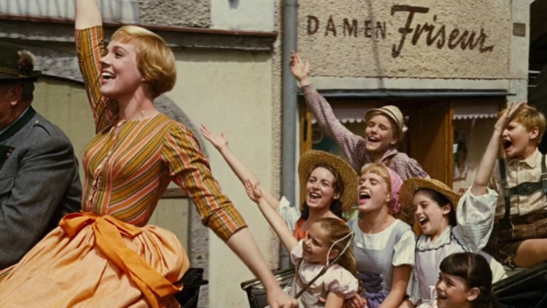A still from 'The Sound of Music' featuring Maria in a cart singing with the von Trapp children.