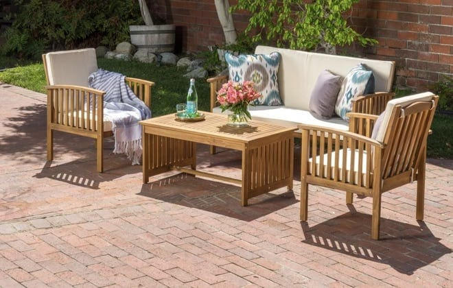 Brick patio with light wooden furniture with white cushions
