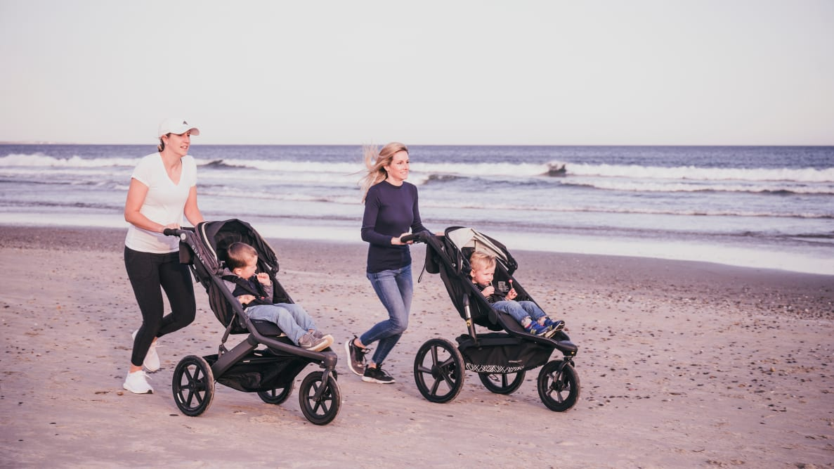 Two women jogging on a beach pushing kids in jogging strollers