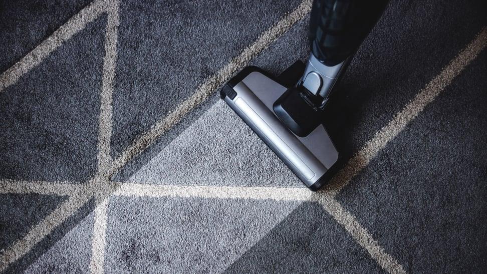 Vacuum cleaning a blue carpet