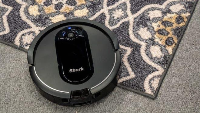 A Shark IQ AV1010AE Robot Vacuum cleaning a carpet.
