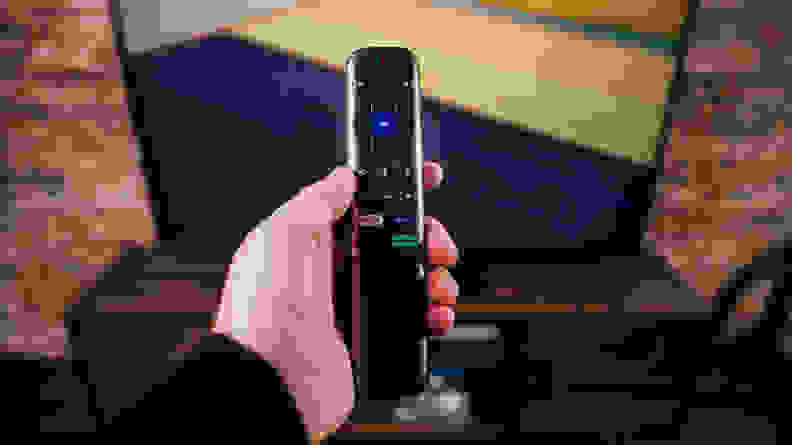 The TCL 6-Series' Roku Remote control being held in front of the screen