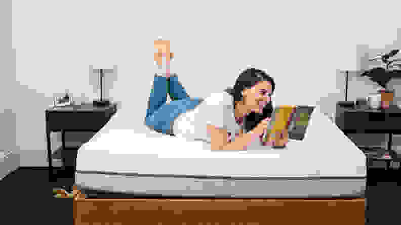 a person lies on their stomach reading on the purple mattress