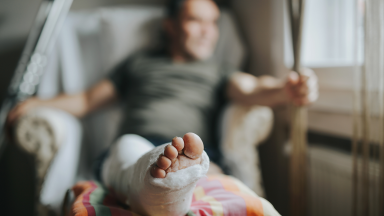 Person looking out window while sitting with injured leg propped up on pillow.