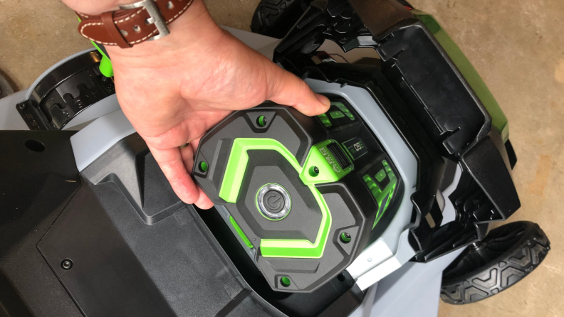 A hand pulls the green Ego Power+ lawn mower battery out of it's spot.