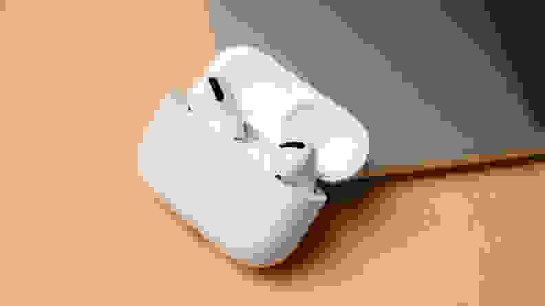 White-colored wireless earbuds lie on a beige desk next to a laptop.