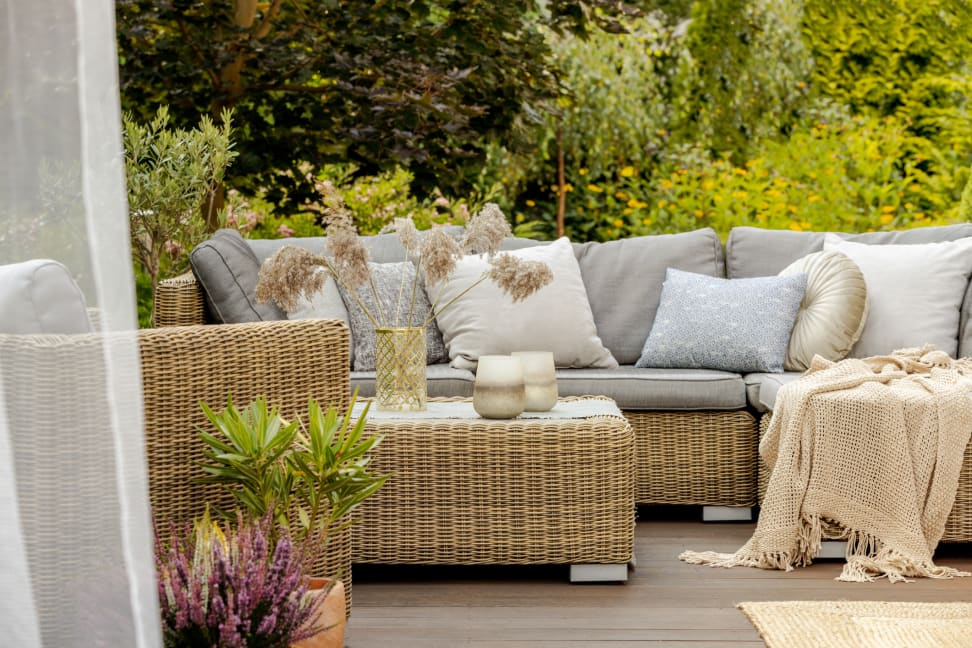Cozy patio furniture with plants, throw pillows, and a blanket.