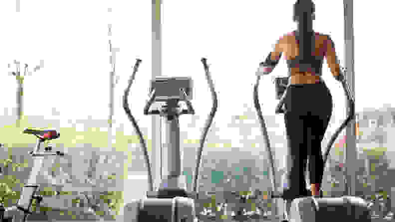 A woman using an elliptical machine looking out the window.